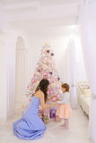Young mother and little daughter decorating Christmas tree and p Stock Photos