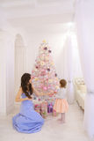 Young mother and little daughter decorating Christmas tree and p Stock Images