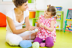 Young mother and little daughter decorating Easter eggs. With colorful yarn strings Stock Images