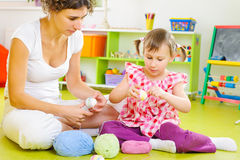 Young mother and little daughter decorating Easter eggs. With colorful yarn strings Royalty Free Stock Images