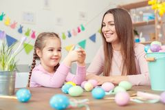 Mother and daughter easter celebration together at home sitting looking at egg smiling Royalty Free Stock Images