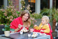 Young mother with little daughter eating ice cream in outdoors cafe Stock Photos