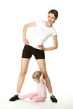 Young mother and little daughter exercising Royalty Free Stock Images