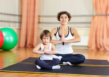 Young mother and little daughter exercising in gym Royalty Free Stock Photography