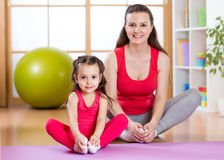 Young mother with little daughter exercising in gym at home Royalty Free Stock Images