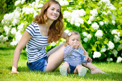 Young mother and little daughter on green grass Stock Photography