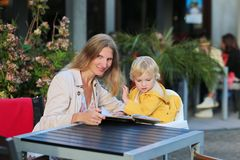 Young mother with little daughter having meal in outdoors cafe Stock Photos