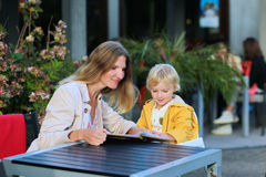 Young mother with little daughter having meal in outdoors cafe Stock Photography