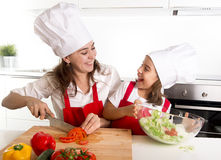 Young mother and little daughter at house kitchen preparing salad for lunch wearing apron and cook hat Stock Image