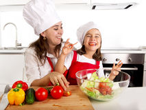 Young mother and little daughter at house kitchen preparing salad for lunch wearing apron and cook hat Royalty Free Stock Images