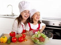 Young mother and little daughter at house kitchen preparing salad for lunch wearing apron and cook hat Stock Photography