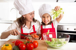 Young mother and little daughter at house kitchen preparing salad for lunch wearing apron and cook hat Royalty Free Stock Photo