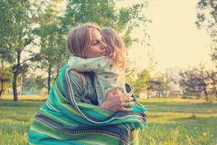 Young mother and little daughter are hugging in park Stock Photos
