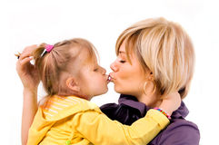 Young mother and little daughter is kissed Royalty Free Stock Image