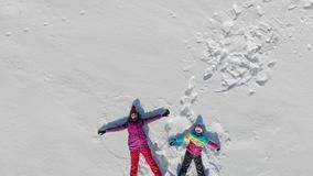 Young mother and little daughter making angels on the snow. Aerial video of cheerful family have fun in sunny winter day. Outdoors stock footage