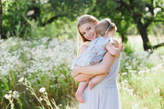Young mother with little daughter on the nature Stock Photos