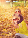 Young mother and little daughter playing fashion dressed in sunglasses in autumn park. Stock Image
