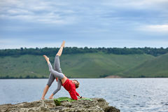 Young mother and little daughter practicing balancing yoga pose on the rock near river. Royalty Free Stock Images