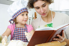 Young mother with little daughter preparing cookies Stock Images