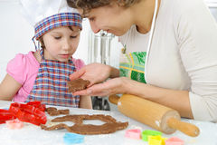 Young mother with little daughter preparing cookies. Young mother with little daughter shaping dough for cookies stock photo