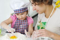 Young mother with little daughter preparing cookies Royalty Free Stock Image