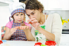 Young mother with little daughter preparing cookies. Young mother with little daughter shaping dough for cookies royalty free stock photography