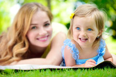 Young mother with little daughter reading book in park Royalty Free Stock Photography