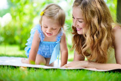 Young mother with little daughter reading book in park Royalty Free Stock Images