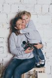 Young mother and little daughter in same clothes standing near wall and hugging Stock Images