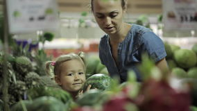 Young mother and little daughter selecting fruits at the supermarket
