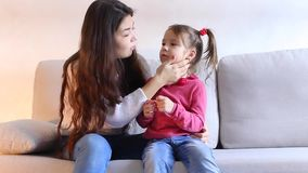 Young mother with little daughter sitting on couch in living room. stock video