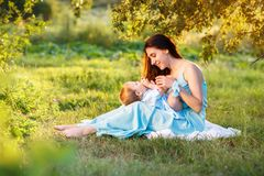 Mother with little daughter playing on green grass Stock Photos
