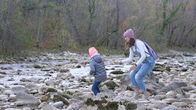 Young mother with little daughter is throwing the stones into the mountain river stock footage