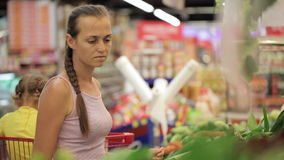 Young mother with little daughter in trolley selecting greens at supermarket. Young attractive mother with little daughter in trolley selecting greens at stock video