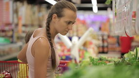 Young mother with little daughter in trolley selecting greens at supermarket. Young attractive mother with little daughter in trolley selecting greens at stock video footage