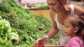 Young mother with little daughter in trolley selecting lettuce at supermarket. Young attractive mother with little daughter in trolley selecting lettuce at stock video
