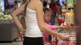 Young mother with little daughter in trolley selecting tomatoes at supermarket. Young attractive mother with little daughter in trolley selecting tomatoes at stock footage