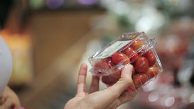 Young mother with little daughter in trolley selecting tomatoes at supermarket stock video