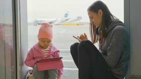 Young mother and little daughter uses the devices at airport. Woman using smart phone and her child playing on the tablet next the window at departure launge Stock Photos