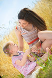 Young mother with little daughter at wheat field Stock Image