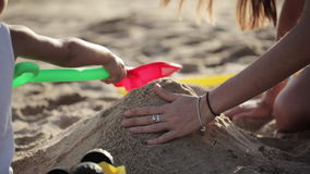 Young mother with little doughter playing with sand on the beach stock video footage