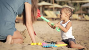 Young mother with little doughter playing with sand on the beach stock footage