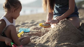 Young mother with little doughter playing with sand on the beach stock video