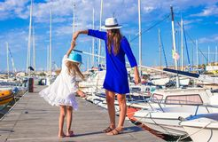 Young mother and little girl in port during summer Stock Photos