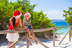 Young mother and little girl in red Christmas hat Stock Images