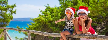 Young mother and little girl in red Christmas hat Royalty Free Stock Photos