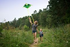 A young mother and a little girl are running along the path with a kite. Summer day, wildflowers. A young mother and a little girl are running along the path stock photo