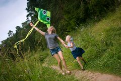 A young mother and a little girl are running along the path with a kite. Summer day, wildflowers stock image