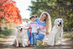 A young mother with a little girl and two dogs on a walk in the Park in autumn Royalty Free Stock Photos
