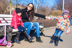 Young mother and little girls have fun at sunny day outdoors Royalty Free Stock Photo
